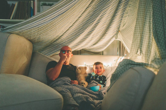 A father and son watching a movie in a fort and eating popcorn.