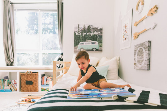 A little boy reading in his bright bedroom.