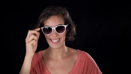 ea2b29f5134b 0:12 Fun young lady tries on white sunglasses, laughs and strikes silly  poses