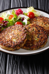 Delicious mushroom vegetable patties served with fresh salad on a plate close-up. vertical
