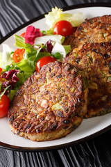 Vegetarian mushroom patty served with vegetable salad close-up on a plate on the table. vertical