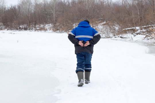 A man walks in the winter and holds on to his back, a beautiful winter nature.