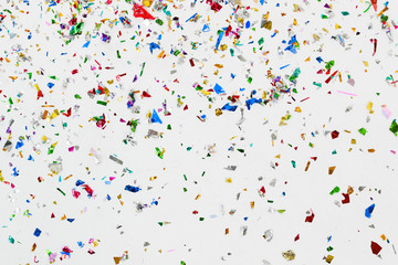 colorful glitter and confetti on white background