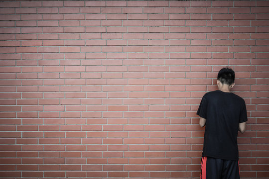 back view of teenage Asian boy standing in front of red brick wall background, copy space, teenager problem concept