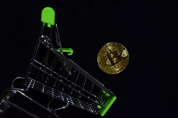 Bitcoin gold and shopping cart on black background. Bitcoin falls from a shopping cart concept