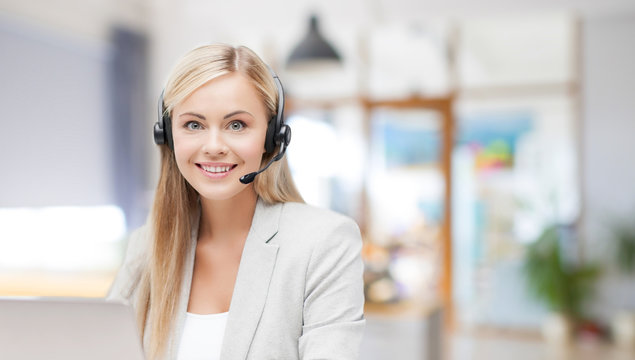 business, technology and communication concept - female helpline operator in headset working at office