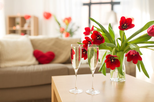 valentines day, romantic date and holidays concept - two champagne glasses and red tulip flowers on table in living room or home