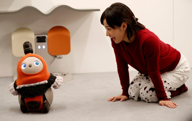 A woman calls up GROOVE X's new home robot LOVOT at its demonstration during the launching event in Tokyo