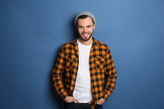 Fashionable young man in checkered shirt on color background