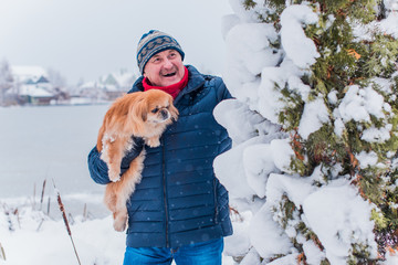Senior man dog lover with his red pekingese pet on a walk at snowy park. Concept love and care of animals. Good people caring for pets