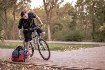Attractive young caucasian man with dark hair on the bicycle in the park, leans towards his bag with sportswear. Outdoors, lovely autumn (fall) day. Copy space
