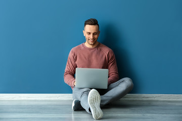 Young man with laptop sitting near color wall Wall mural