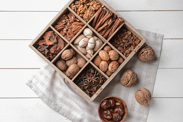 Assortment of nuts and spices in divided box on white wooden table