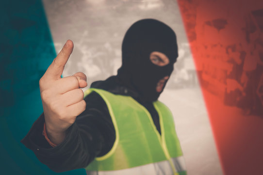 concept of street protests of workers, proletarians against system, bourgeoisie. Yellow vests protest against higher fuel prices in France. man in a mask and a yellow vest on background of French flag