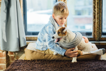 Blond finn boy with his friend Jack russel terrier hugging and wrap up in grey knitted scarf near the window in winter time at home.