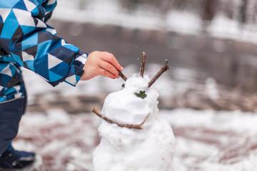 Child playing in park with a snowman. Kind spielt in park mit Schneemann.