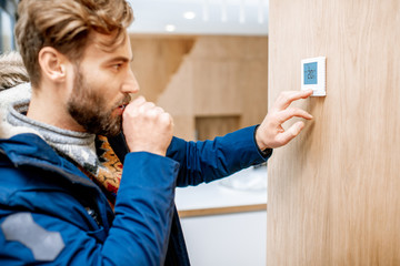 Man in winter clothes feeling cold adjusting room temperature with electronic thermostat at home