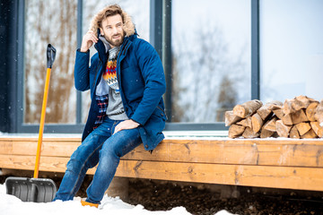 Portrait of a handsome man in winter clothes filling cold sitting on the terrace of the modern house