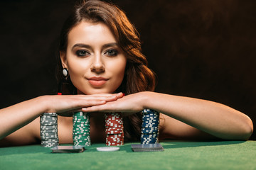 attractive brown haired girl leaning on poker chips and looking at camera isolated on black Wall mural