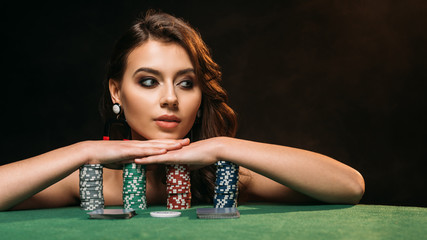 beautiful brown haired girl leaning on poker chips and looking away isolated on black Wall mural