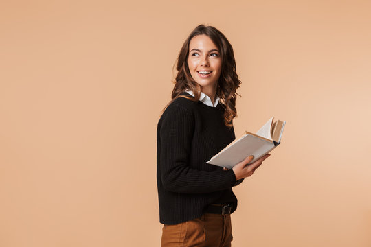 Photo of gorgeous woman 20s holding book while looking back, isolated over beige background