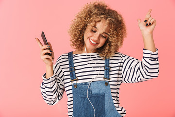 Image of charming curly woman 20s listening to music on smartphone via earphones, isolated over pink background