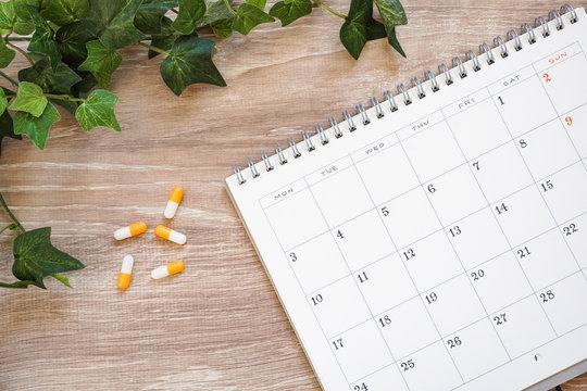 Medicine and calendar. Image of hospital visit date or medicine drinking date. 薬とカレンダー 通院日や薬を服用する日などのイメージ