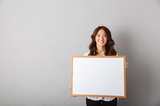 Cheerful asian woman standing isolated over gray