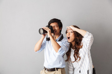 Excited asian couple standing isolated over gray