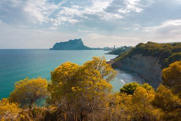 Beautiful Mediterranean turquoise blue sea coastline with rocks, green plants and trees. Summer autumn season. View of sea horizon and big crag mountain. Calpe, Alicante, Community of Valencia, Spain