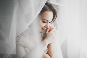 Gorgeous bride in robe posing and preparing for the wedding ceremony face in a room
