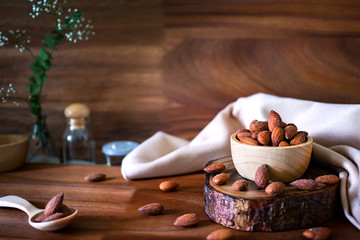 Almond in wooden bowl on wooden table. Concept with copyspace.