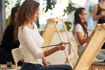 Young charming girl with brown curly hair dressed in white blouse paints a picture at the easel in the drawing school