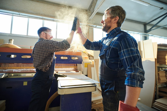 Positive satisfied bearded factory workers standing at workbench with particleboard and making dusty high five while greeting each other at workplace