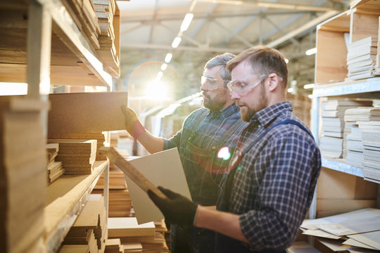 Serious brutal workers in safety goggles standing at shelves full of wooden details and choosing furniture pieces for assembling in warehouse