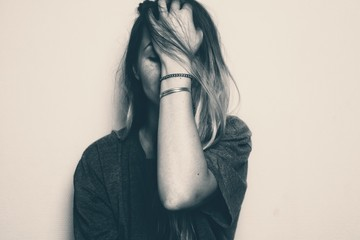 Blonde girl covering her face with her left hand. Image in black and white noir. Depicting sad,...