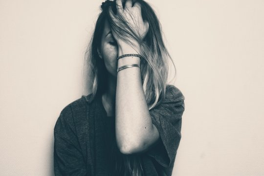 Blonde girl covering her face with her left hand. Image in black and white noir. Depicting sad, worried, frustrated emotion, like the female messed up or is stressed about something, unhappy, unsure