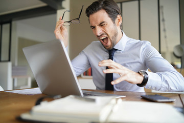 Angry businessman losing patience and screaming at laptop in modern office