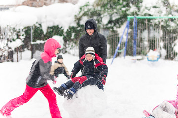 Kids playing in snow. Children play outdoors in winter snowfall.