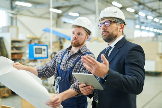 Serious confident business investor in glasses gesturing hand while asking question to young engineer,  businessman visiting factory and talking to engineer