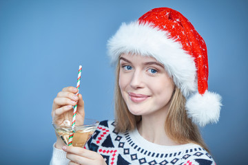 Woman wearing Santa hat holding martini glass with a straw