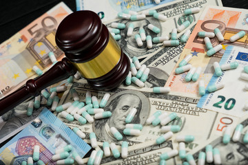 Wood judge's gavel and scattered colorful drugs on the dollar and euro cash background