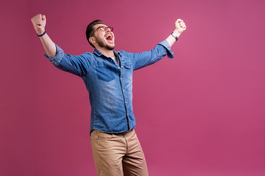 Portrait of a satisfied young man celebrating success isolated over pink background.