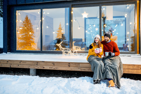 Young couple warming up with plaid and hot drinks sitting on the terrace of the modern house in the mountains durnig the winter holidays