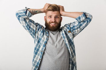 Happy bearded man dressed in plaid shirt standing
