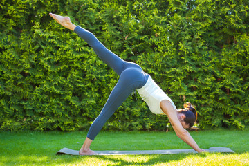 adult woman doing yoga in sunny morning park