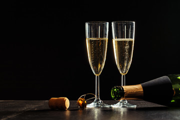 bottle of champagne and glasses over dark background