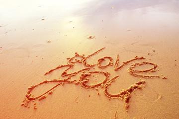 Love letters handwritten in sand on beach