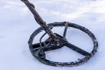 The metal detector lies in the snow, in search of treasure in the winter. winter excavations