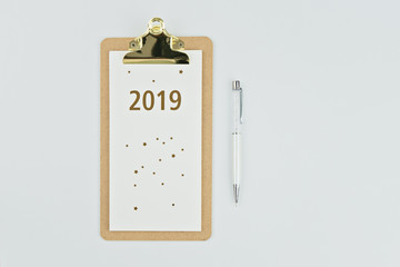 New year 2019 calendar with notebook and pen on white background with copy space, flat lay style. New beginnings planning concept